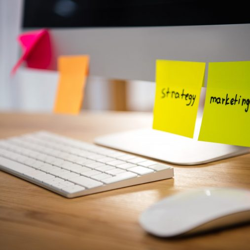 close up view of colorful sticky notes with marketing and strategy lettering on computer screen at