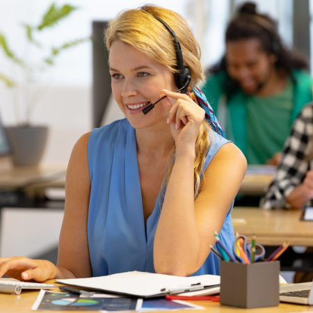 Front view of happy Caucasian female customer service executive talking on headset and working on computer in a modern office
